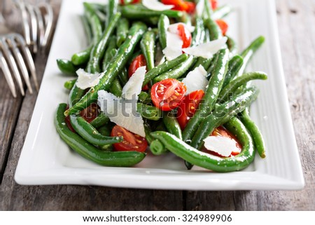 Warm salad with green beans, tomatoes and parmesan cheese - stock photo