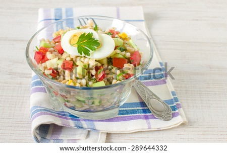 Warm salad with red and yellow pepper, barley, cucumber, tomato and egg - stock photo