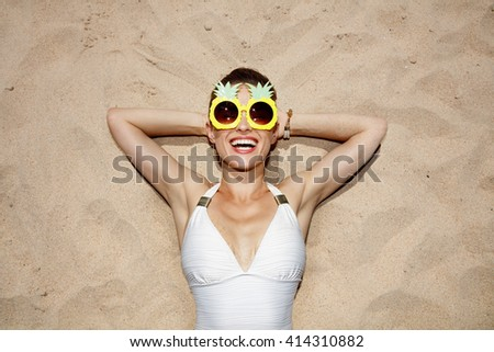 Warm sand treatment. Portrait of smiling woman in swimsuit and funny pineapple glasses laying on the sand - stock photo