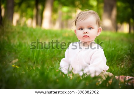 Warm spring time in the park. Little blond caucasian girl sitting in the green grass. Girl thoughtfully looking into the camera - stock photo