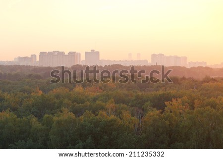 warm summer sunrise over urban houses and park in early morning - stock photo