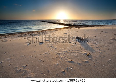 warm sunset over sand beach on North sea, Holland - stock photo