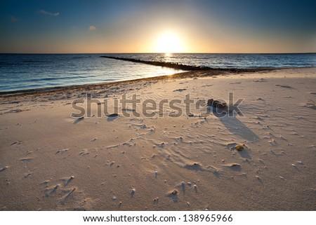 warm sunset over sand beach on North sea, Holland - stock photo