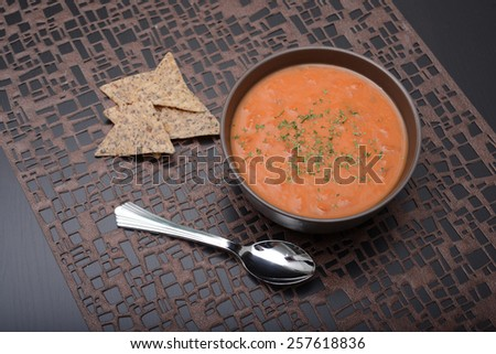 warm tomato soup and chips - stock photo