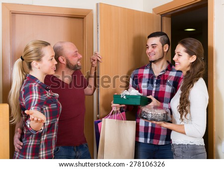 Warm welcome of happy friends holding gifts and sweets - stock photo