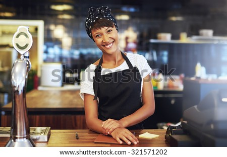 Warm welcoming young business entrepreneur standing behind the counter in her cafe giving the camera a beaming smile of welcome - stock photo