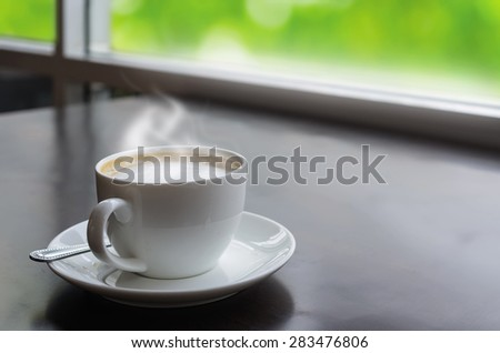Warm white coffee cup on the table. With the backdrop of a beautiful Nature background. - stock photo