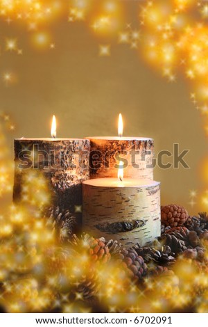 Warm Winter Glow:  three lit birch tree candles nestled among pine cones surrounded by warm, twinkling (digital) embers.  Holiday/winter/fall concept. - stock photo