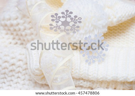 Warm woolen knitted hat and scarf with big white snowflakes - stock photo