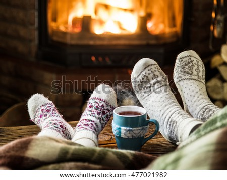 Warming and relaxing near fireplace. Mother and daughter with the cup of hot drink in front of fire.
