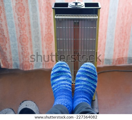 Warming of feet a heater with a quartz lamp in the cold room - stock photo