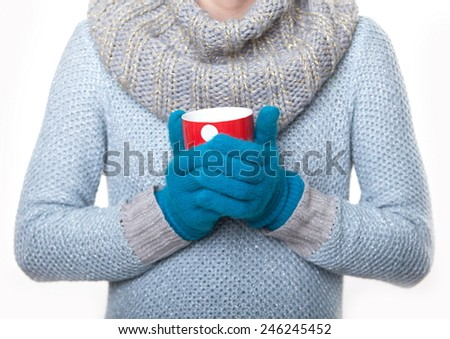 Warming red mug of tea. Girl warm gloved hands on a mug - stock photo