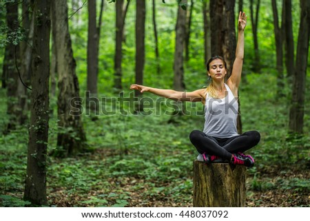 Warming-up. Beautiful sporty girl in the woods on a stump in yoga, sports - stock photo