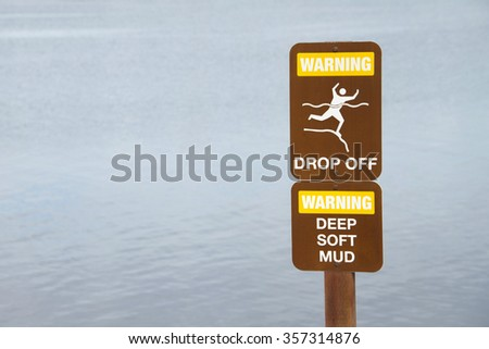 Warning drop off sign near cliff by waters edge. Water in background - stock photo