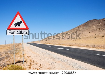 """Warning of road sign - hyenas on the road with description """"for 40 km"""" , Namibia - stock photo"""