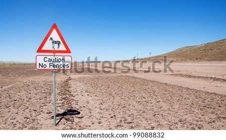 "Warning of road sign - zebras on the road with description ""caution no fences"" , Namibia - stock photo"