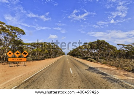 Warning road-sign with information about wild life animals along unfenced road - Eyre Highway in SOuth AUstralia on a sunny summer day. - stock photo