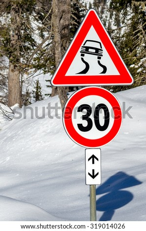 Warning Sign and Speed Limit on a Road Covered in Snow. Danger of Skidding on Ice and Snow. - stock photo