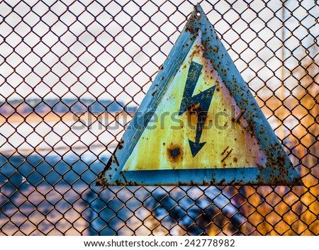 "Warning sign ""Caution voltage"", posted on the fence restricted area. - stock photo"