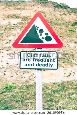 Warning sign for falling rocks from a cliff in the UK with retro filter applied - stock photo