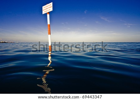warning sign in the sea waves - stock photo