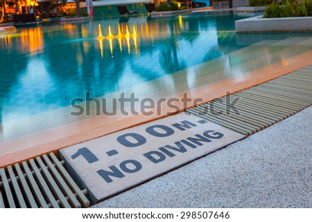 """warning sign """"1.00m No Diving"""" at Swimming pool of luxury hotel - stock photo"""