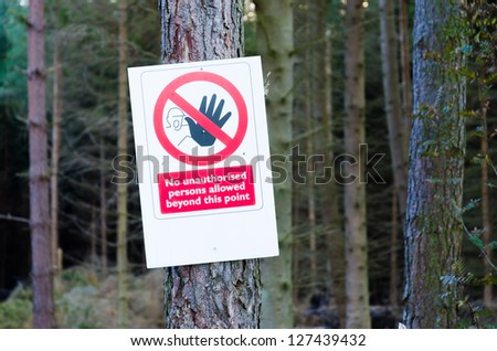 Warning sign nailed to tree in forest - stock photo