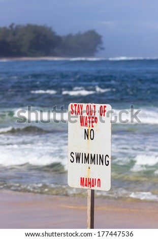 Warning sign no swimming in treacherous winter waters on Tunnels Beach in Kauai Hawaii - stock photo