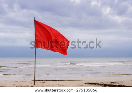 warning sign of a red flag at a beautiful beach with a blue sky and a turquoise sea - stock photo