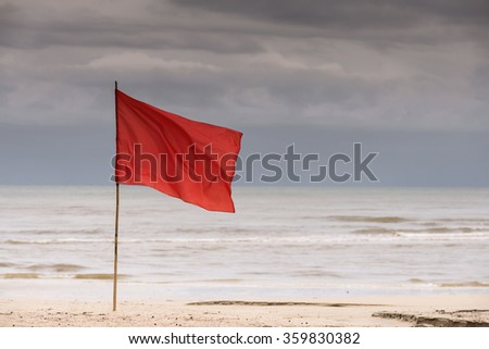 warning sign of a red flag on beach. (dark sky) - stock photo