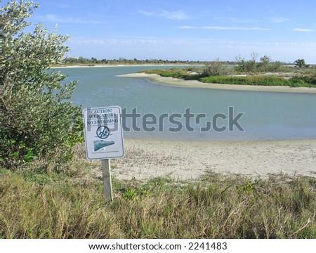 Warning sign on beach of tropical lagoon - stock photo
