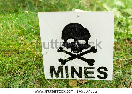 warning sign, warning landmines in this field! - stock photo