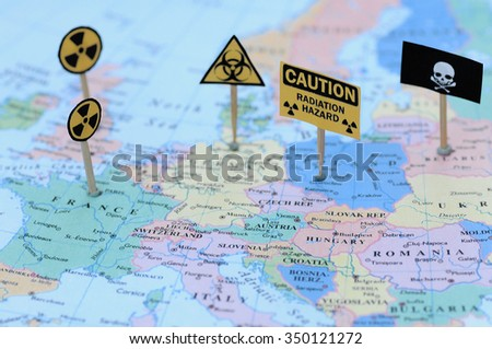 Warning signs including a skull, biohazard warning, nuclear warning and radiation hazard on a map of Europe - illustration image. Selective focus (nuclear hazard is focused, the others are unfocused) - stock photo