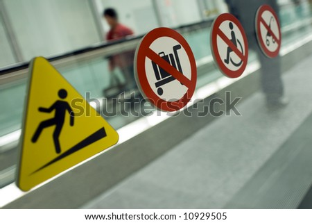 Warning signs on a moving walkway in a major North American airport. (Shot with minimum depth of field. Focus is on the second symbol from the left.)