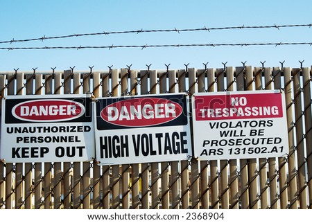 Warning signs restricting access an area containing high voltage equipment. - stock photo
