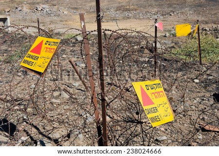 Warning signs with 'Danger Mines' written on it at a mine field on the Golan Heights in Israel - stock photo