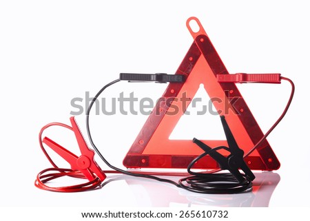 warning triangle and jump start cables isolated on white - stock photo