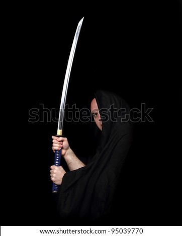 Warrior Holding a Samurai Sword isolated on black - stock photo