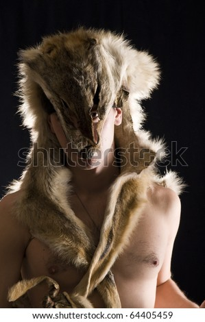 Warrior in the wolf skin. Low key studio shot - stock photo
