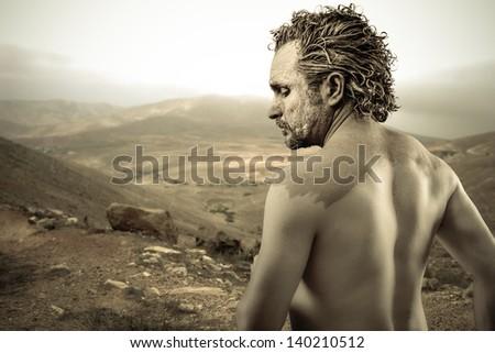 Warrior man covered in mud on desert background - stock photo