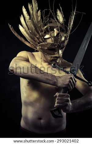 Warrior with helmet and sword with his body painted gold dust - stock photo