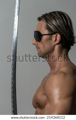 Warrior With Long Sword Over Grey Background - Portrait Of A Handsome Muscular Ancient Warrior With A Sword - stock photo