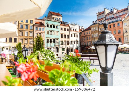 Warsaw old town marketplace square, street lamp in cafe and flowers on foreground - stock photo