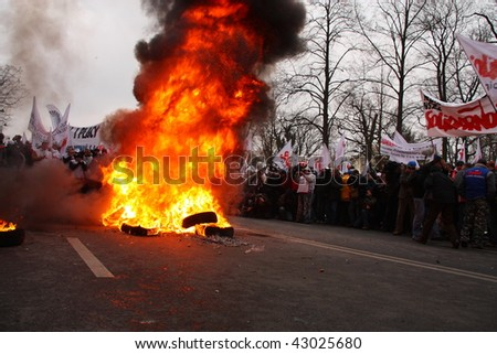 WARSAW, POLAND - DECEMBER 15: Protesters watch burning tires in the street during anti government Solidarity demonstration on December 15, 2009 in Warsaw, Poland. - stock photo