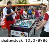 WARSAW, POLAND - JUNE 16: Polish football fans enjoying their time in Warsaw, playing outdoor table soccer before UEFA EURO 2012 football match vs. Czech team, June 16, 2012 in Warsaw, Poland - stock photo