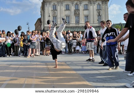 WARSAW, POLAND - JUNE 28, 2009: Street dancer performs breakdance moves at Warsaw's Old Town.  - stock photo