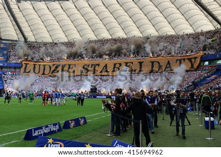 WARSAW, POLAND - MAY 2, 2016: Legia Warsaw fanatical fans lighting smioke flares during Polish Cup final football match between Legia Warszawa and Lech Poznan at the National Stadium in Warsaw. - stock photo