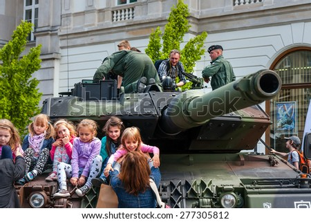 WARSAW, POLAND - MAY 08, 2015: Leopard 2 tank and  children learning about army, during the public celebrations of 70th Anniversary of End of WW II - stock photo