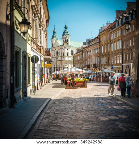 Warsaw, Poland - May 17, 2013. People walking in old and narrow cobblestone street of Warsaw, Poland, Europe. Beautiful sunny day, old church in background. Unesco world heritage sight.