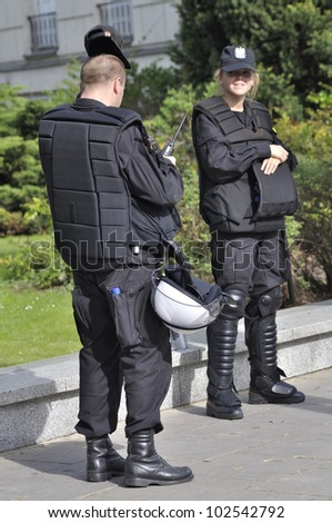 WARSAW, POLAND - MAY 11: Police officers in riot gear, protecting a parliament building, during a protest of the Solidarity trade union against the pension reform on May 11, 2012 in Warsaw, Poland. - stock photo
